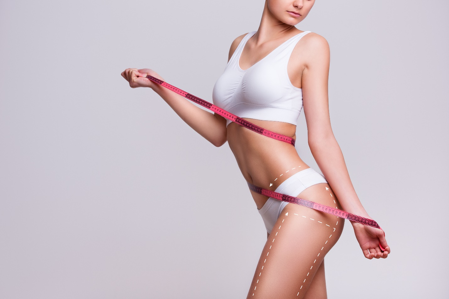 A female model with a body measuring tape showing the effects of liposuction.